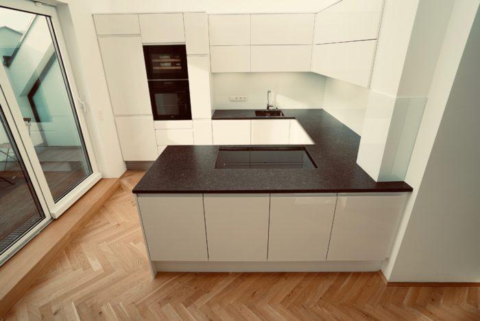 einbauküche mit griffräsung | stein arbeitsplatte | nischen rückwand beleuchtung